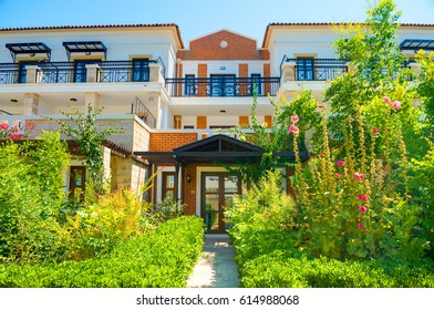 CRETE ISLAND, GREECE, JULY 01, 2011: View on hotel luxury vip villas for tourists guests. Green tropical trees hotel garden. Classic Greek architecture. Greece island holidays vacations tours