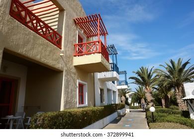 Crete Island, GREECE - MAY 11, 2014:  Building with red balcones and palms in high class greek hotel Aldemar Cretan village, Crete island, Greece.