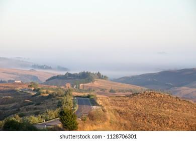 Crete Senesi landscape in Tuscany, Italy on a foggy summer dawn