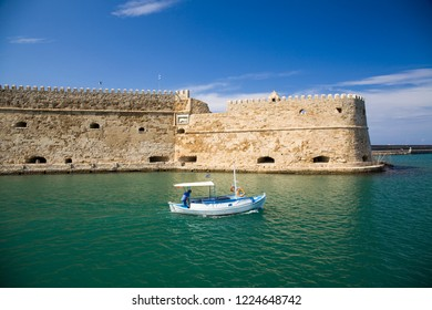Crete,Heraklion/Greece - September 27, 2018:Boat under the walls of Koules Fortress in Heraklion. Fortress on the sea, tourist attraction of the city of Heraklion. Historic building in Crete, Greece.