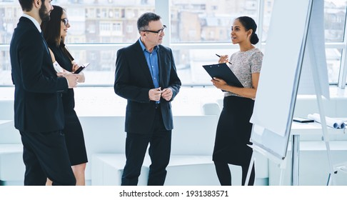 Crew of confident male and female colleagues discussing ideas for productive work in own company,group of business people talking about entrepreneurship and collaboration in board room with flip chart