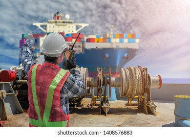 Crew controlling the hydraulic mooring winch mechanism with hawser on board at forward near Mooring winch and worker holding radio talkie- walkie control operate and cargo container ship background.