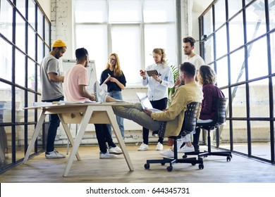 Crew of creative marketing experts presenting to experienced project manager of company sitting with laptop computer  ideas for advertising campaign using flip chart on informal conference meeting