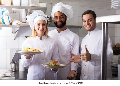 Crew of happy spanish professional cooks working at restaurant kitchen