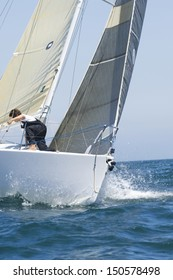 Crew member on a cropped yacht competing in team sailing event