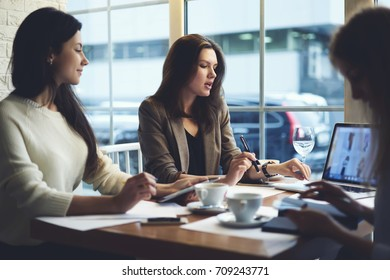 Crew of professional designers having discussion about new fashion collection promotion on web site, female marketing experts analyzing information during working process n cafe interior using devices