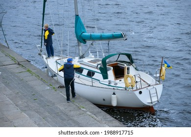 Crew of sailing yacht yachtsmen moor to a berth using ropes. Amateur regatta devoted to the Day of city. May 30, 2021. Kyiv, Ukraine
