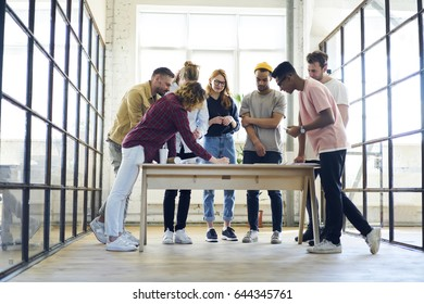 Crew of skilled young architects standing near table with blueprints discussing ideas about improving project planning,students collaborating on coursework drawing outlay sharing opinion on lesson
