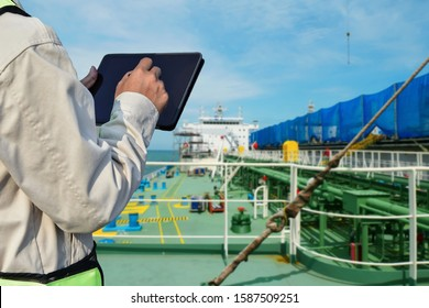 crew worker on tanker ship and hand holding iPad on green pipe line background
