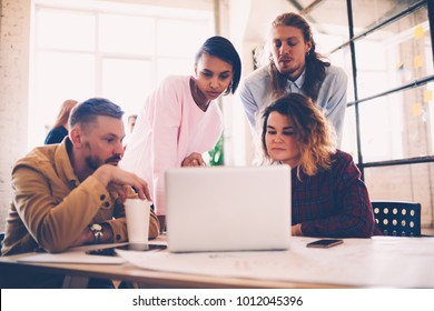 Crew of young female employees showing to male coach startup planning on laptop computer,skilled web designers collaborating on project reading information on website during meeting in office