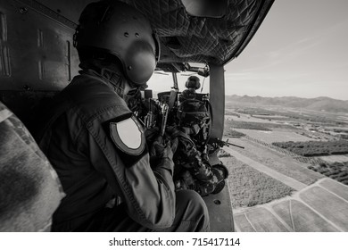 Crewman looks out of door of military helicopter