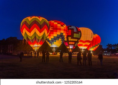 The crews of 5 dawn patrol hot air balloons are preparing their balloons for launch. They are lined up, fully inflated and glowing in the early morning light of dawn. Silhouetted people are in front.