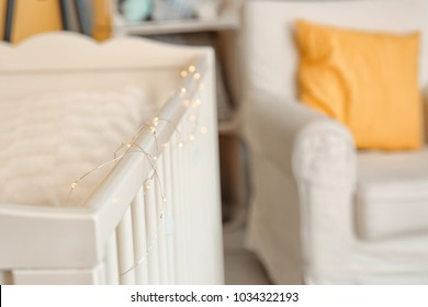 Crib with garland in children's room, closeup