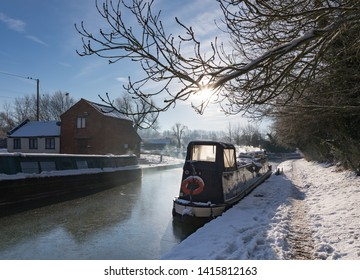 Crick, Northamptonshire / UK - December 12th 2017: Low-lying winter sun shines on a frozen canal and snow-covered towpath at Crick Wharf. Smoke from a stove on a narrowboat hangs in the air.