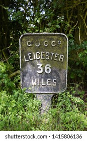 Crick, Northamptonshire / UK - June 4th 2019: Iron canal milepost on the towpath of the former Grand Junction Canal Company canal, showing the distance of 36 miles to Leicester.