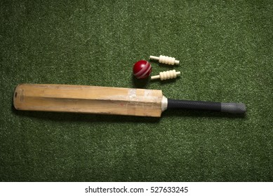 Cricket ball, bat and bails on lawn with copy space