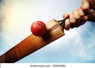 Cricket batsman hitting a ball shot from below against a blue sky