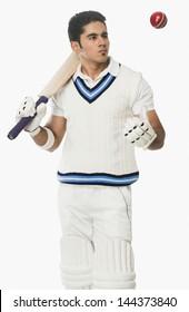 Cricket batsman holding a bat and looking at a ball
