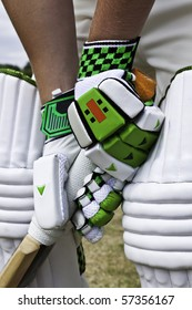 Cricket batsman stood at the crease wearing protective gloves and pads