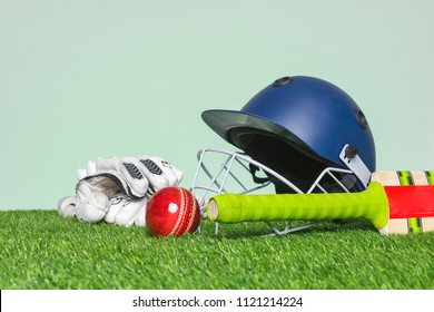 Cricket equipment with bat, ball, helmet and gloves on grass with green background.