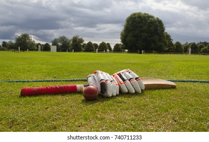 Cricket gloves and bat on the boundary line during match in English village.