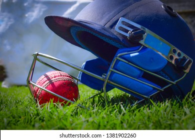 Cricket halmet and a ball on a green grass. Helmet protects batsman from fast balls which may otherwise cause harm to playing person.