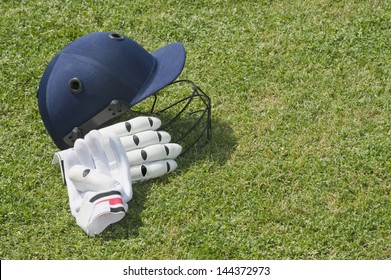 Cricket helmet and batting gloves in a field