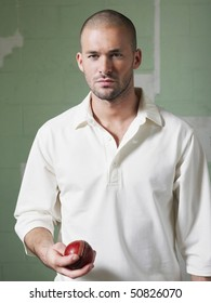 Cricket player holding ball, portrait