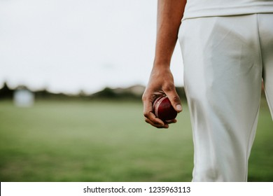 Cricket player holding a leather ball