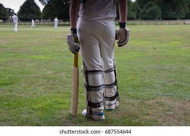 Cricketer standing on boundary waiting to bat in English village match.