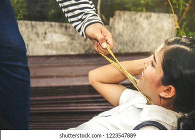 Crime concept : The bandit pulls a gold necklace on a woman's throat to steal precious belongings.