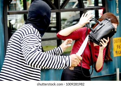 Crime concept : The masked bandit use a threatening knife to steal precious belongings from a woman who walks alone and is frightened.Selective Focus