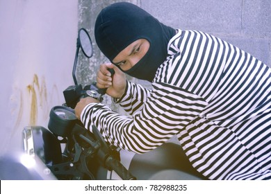 Crime concept : Motorcycles theft : Masked robbers use tools to tweak the black motorbike with a careful look.