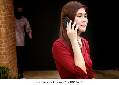 Crime concept : The thief assaulted the girl who was standing on the phone : The masked bandit hide in the dark, looking at the woman who was standing on the phone, hoping for mischief.Selective Focus