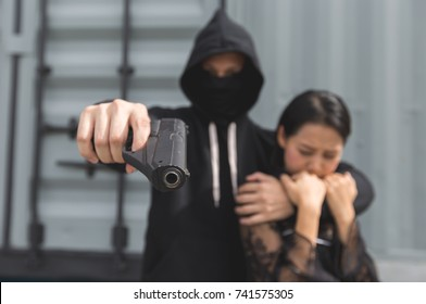 Crime concept. Thief was threatening hostage with gun.
