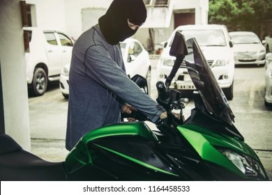 Crime concept : Thieves steal green motorcycle and unlock the target car in the parking lot under the building.