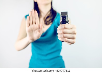Crime Concept. Young Woman Holding Pepper Spray Closeup On White Background
