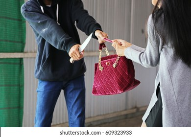 crime concepts; robbery concepts; a robber aimed his sharp knife at a woman to rob her valuable things in bag