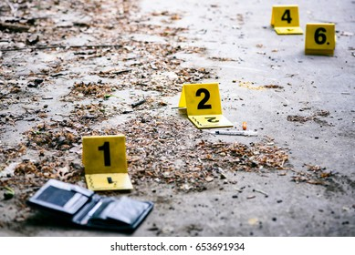 Crime investigation, yellow crime scene marker next to wallet on the ground