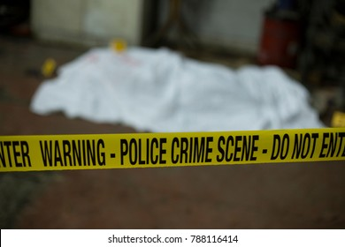 Crime scene band and covered dead body in background.