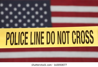 Crime scene barrier tape over out of focus US flag