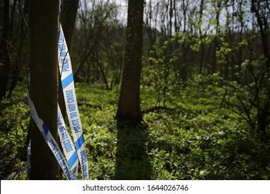 Crime scene behind police tape in the sunny woodland
