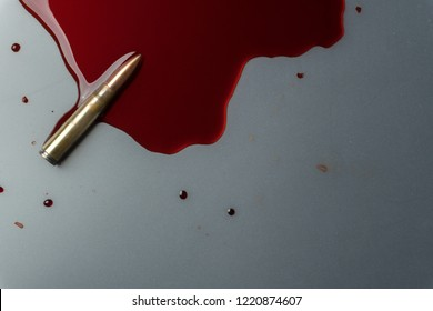 crime scene concept, close up of a gun bullet in pool of blood
