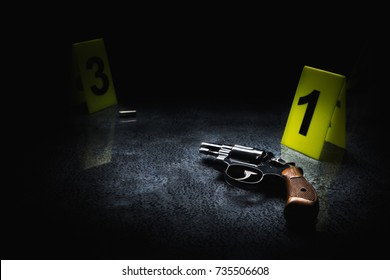 Crime scene concept with a gun and evidence markers / high contrast image