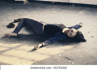 Crime scene concept photo of a murder victim woman lying dead on the ground of old building.