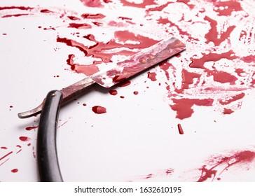 Crime scene concept. Vintage straight razor in pool of blood.Blood splatter and barber razor. Straight razor.