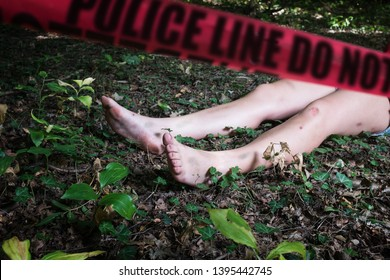 """Crime scene with a dead body and red cordon tape, naked female legs lying in grass and leaves in forest with red """"POLICE LINE DO NOT CROSS"""" tape, recreation of a homicide scene, murder concept"""