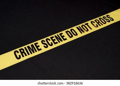 Crime scene do not cross yellow warning sign on black