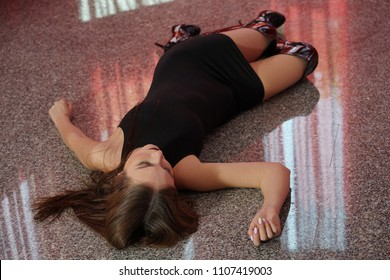 Crime scene - female victim lying on the floor in short dress and boots