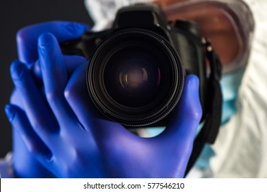 Crime scene forensics investigator with digital camera taking pictures as evidence for the investigation